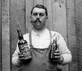 Old photo of guy holding old whiskey bottle and smoking a cigar.